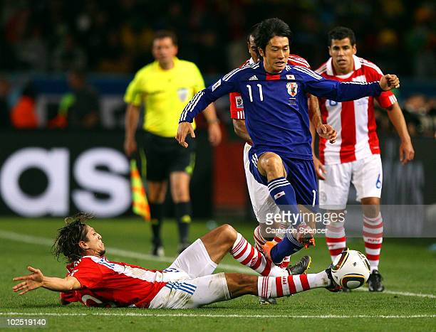 Enrique Vera of Paraguay tackles Keiji Tamada of Japan during the 2010 FIFA World Cup South Africa Round of Sixteen match between Paraguay and Japan...