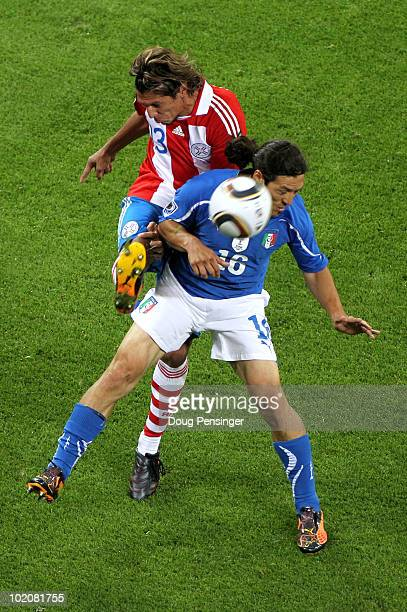 Enrique Vera of Paraguay tries to reach the ball around Mauro Camoranesi of Italy during the 2010 FIFA World Cup South Africa Group F match between...