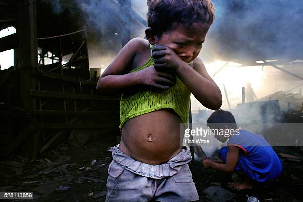 Enrique wipes the soot from his face while collecting wood for charcoal production in the squatter community in the North Harbour of Manila, where...