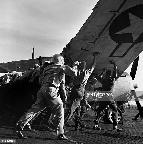 Ens V A Prather directs the deck crew of the USS Lexington as they move a damaged plane out of the way December 1943 | Location USS Lexington