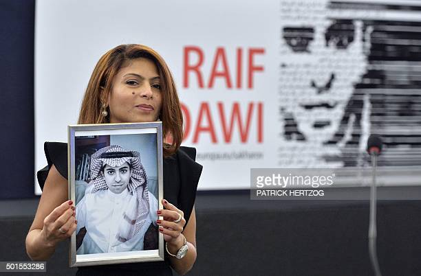 TOPSHOT Ensaf Haidar holds a picture of her husband Raif Badawi after accepting the European Parliament's Sakharov human rights prize on behalf of...