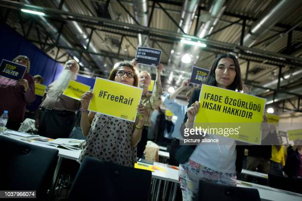 Ensaf Haidar  the wife of jailed Saudi blogger Raif Badawi holds a placard that reads '#FreeRaif' after her speech as a guest at the annual meeting...