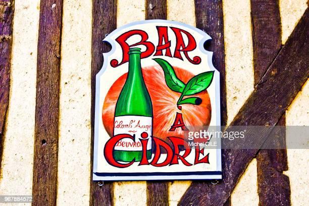 Enseigne une pomme et une bouteille de cidre informant 'bar à cidre' Beuvron en Auge Calvados France