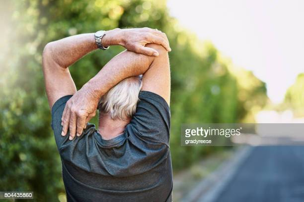 ensuring less chance of injury during his workout - warming up stock pictures, royalty-free photos & images