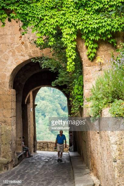 entering italy's magical medieval village of civita... - civita di bagnoregio foto e immagini stock