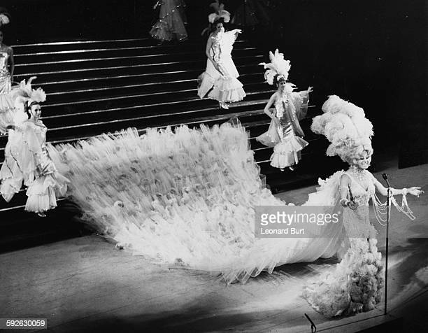 Entertainer and drag artist Danny la Rue wearing a spectacular costume with a long train costing £2000 and made of lace and feathers during...