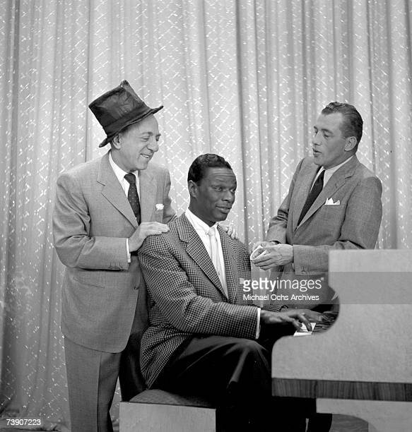 "Entertainer and pianist Nat ""King"" Cole performs a song on piano as television show host Ed Sullivan looks on on ""The Ed Sullivan Show"" on May 16,..."
