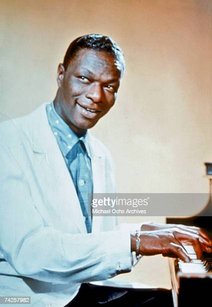 Entertainer and pianist Nat King Cole poses for a portrait sitting at the piano in circa 1960