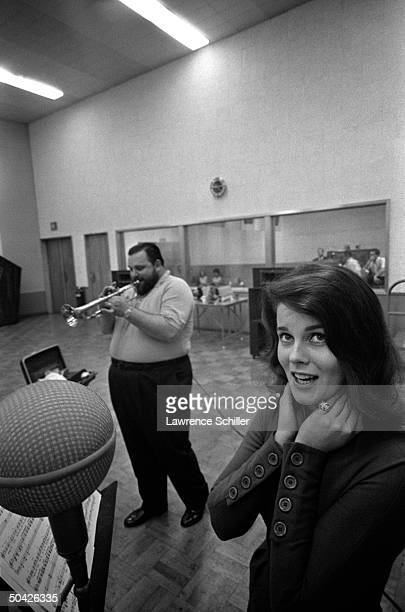 Entertainer AnnMargret singing into huge mike as Al Hirt plays trumpet in bkgrd during recording of album Beauty the Beard