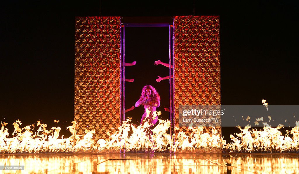 Entertainer Beyonce performs on stage during 'The Mrs. Carter Show World Tour' at the Toyota Center on July 15, 2013 in Houston, Texas. Beyonce wears a custom gold and flesh-toned one piece by The Blonds, Stuart Weitzman shoes and hosiery by Capezio.