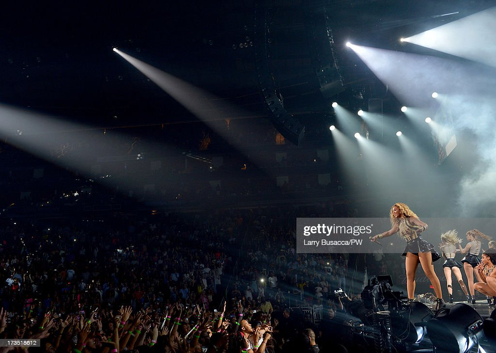 Entertainer Beyonce performs on stage during 'The Mrs. Carter Show World Tour' at the Toyota Center on July 15, 2013 in Houston, Texas. Beyonce wears a gold and black one piece with a skirt by David Koma, Stuart Weitzman shoes and hosiery by Capezio.