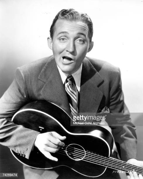 Entertainer Bing Crosby plays an acoustic guitar and makes a funny face in a portrait in 1938