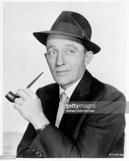 Entertainer Bing Crosby smokes a pipe as he poses for a portrait in circa 1955