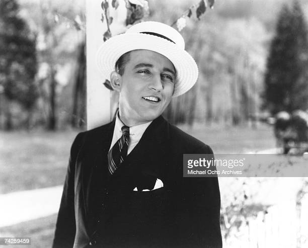 Entertainer Bing Crosby wears a white hat as he performs in a still from a movie in circa 1940
