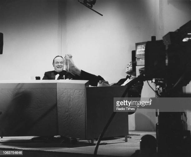 Entertainer Bob Hope laughing as he watched actor Derek Nimmo put his bare feet on a table whilst recording a television show circa 1970
