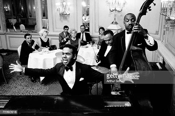 Entertainer Bobby Short performing with his band probably at the Cafe Carlyle