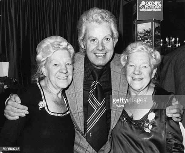 Entertainer Danny la Rue the famous female impressionist with his arms around the 'Dolly Sisters' Ivy and Gladys attending a fund raising bazaar at...