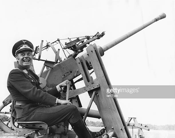 Entertainer Danny la Rue wearing a German 'SS' uniform as he sits at an antiaircraft gun filming scenes for the film 'Our Miss Fred' at an airfield...