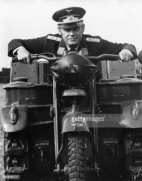 Entertainer Danny la Rue wearing a German 'SS' uniform as he sits on an army motorcycle filming scenes for the film 'Our Miss Fred' at an airfield in...