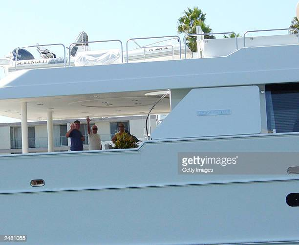 Entertainer Johnny Carson waves from his yacht the Serengeti as his wife Alexis and an unidentified person stand nearby August 29 2003 in Marina del...