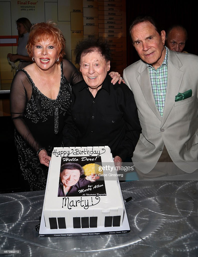 Entertainer Karon Kate Blackwell, her husband, actor/comedian Marty Allen and impressionist Rich Little hold up a cake to celebrate Allen's 93rd birthday during a meet and greet after his performance at the Downtown Grand Hotel & Casino on March 23, 2015 in Las Vegas, Nevada.