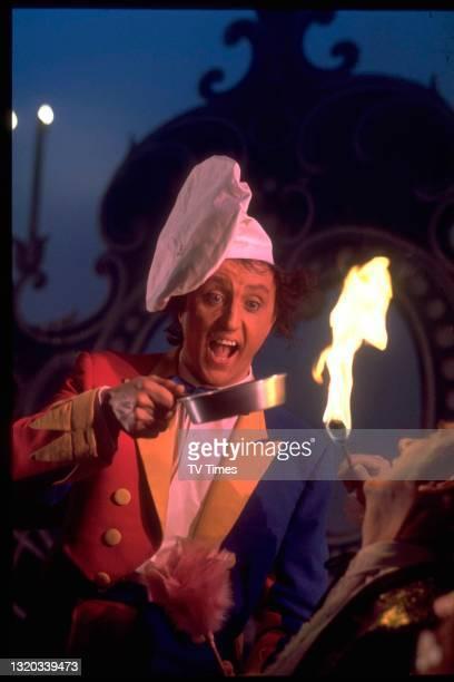 Entertainer Ken Dodd holding a frying pan above a circus fire breather, circa 1971.
