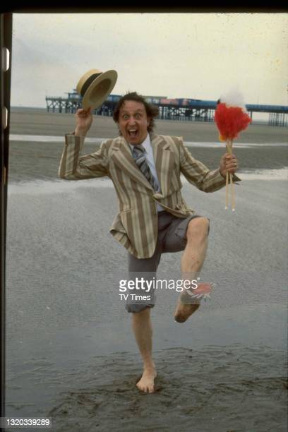 Entertainer Ken Dodd photographed on the beach with a crab pinching his foot, circa 1980.