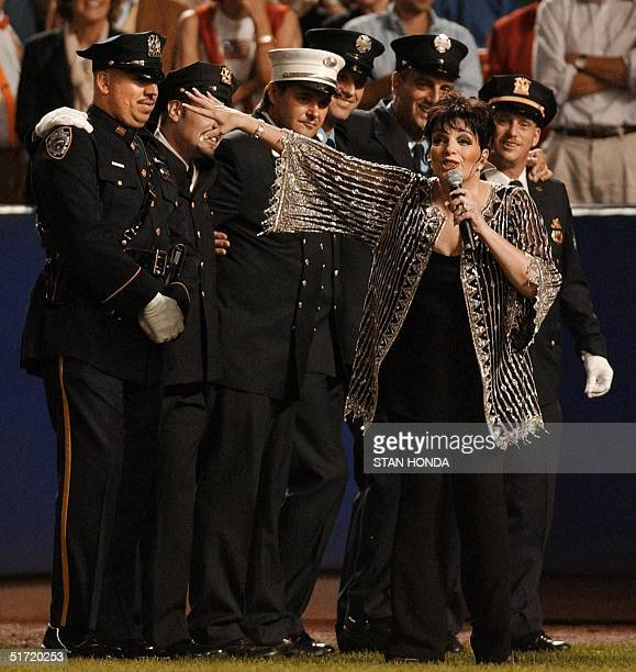 Entertainer Liza Minnelli sings 'New York New York' with a lineup of New York City police and firemen during the seventh inning stretch of the New...