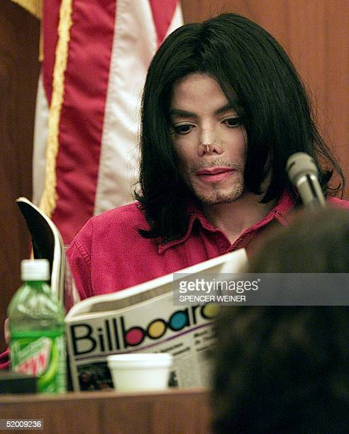 US entertainer Michael Jackson reads a Billboard magazine in Santa Maria Superior Court 13 November 2002 in a trial in which he is accused of...