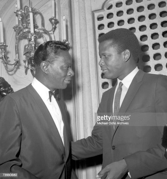 """Entertainer Nat """"King"""" Cole chats with actor Sidney Poitier at the 35th Academy Awards ceremony which was held at the Santa Monica Civic Auditorium..."""