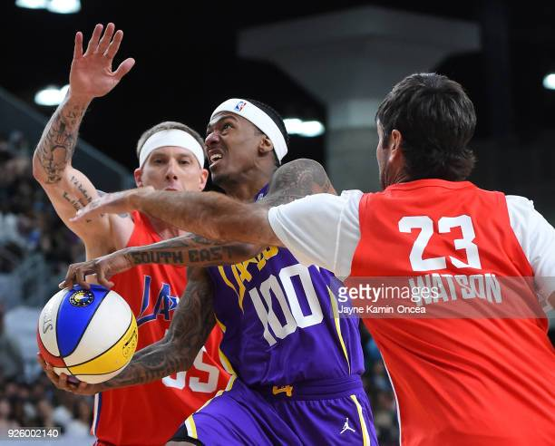 Entertainer Nick Cannon drives to the basket past former NBA player Jason Williams and professional golfer Bubba Watson during the 2018 NBA AllStar...