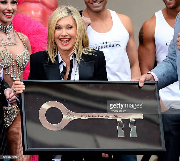 Entertainer Olivia NewtonJohn reacts as she receives a ceremonial key to the Las Vegas Strip during a welcome event at Flamingo Las Vegas on April 2...
