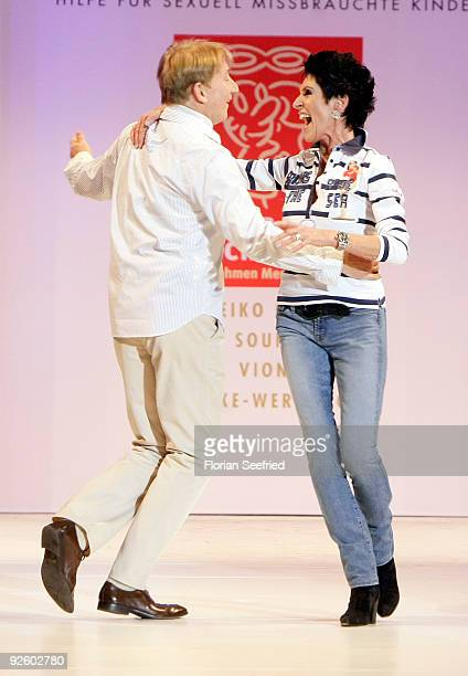 Entertainer Robert Kreis and writer Erika Berger dance on the runway at the 'Event Prominent 2009' fashion show at the Hotel Grand Elysee on November...