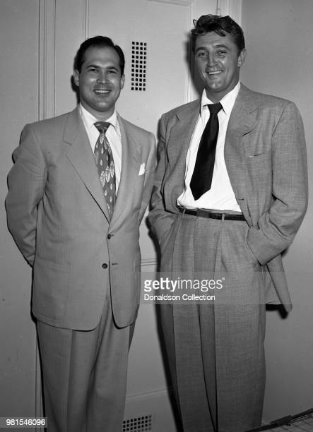 Entertainer Robert Mitchum poses for a portrait with bandleader Joe Reisman at the SherryNetherland Hotel on August 30 1951 in New York