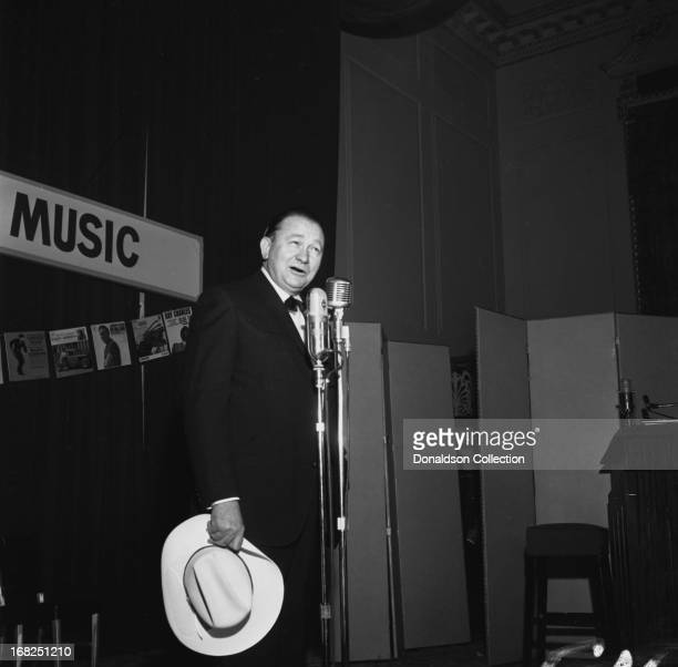 Entertainer Tex Ritter demonstrates the Nashville sound for the Country Music Association during a luncheon and recording session for the promotional...