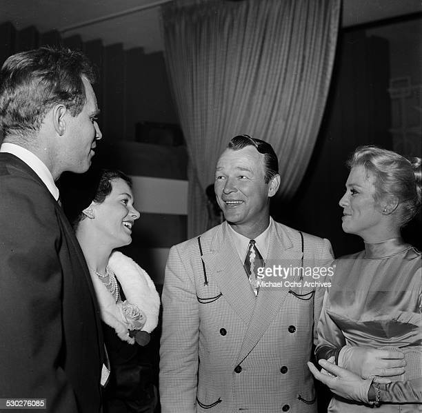Entertainer Tex Ritter his wife Dorothy Fay talk with actor Charlton Heston and his wife Lydia Clarke as they attend the Cinema Editors Awards in Los...