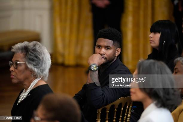 Entertainer Usher looks on before U.S. President Joe Biden signs the Juneteenth National Independence Day Act into law in the East Room of the White...