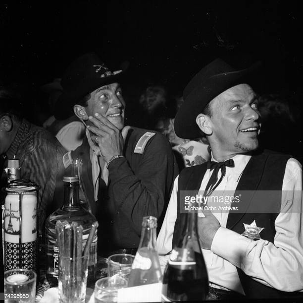 Entertainers and Rat Pack members Dean Martin and Frank Sinatra enjoy dinner wearing cowboy costumes in circa 1960