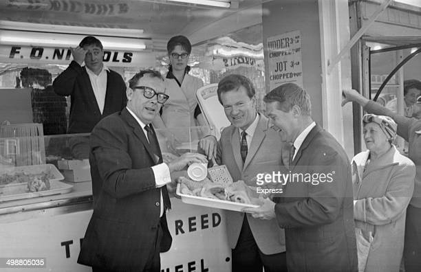 Entertainers Eric Morecambe Ernie Wise and musician Bert Weedon eating tripe from a food stall in Yarmouth 1964