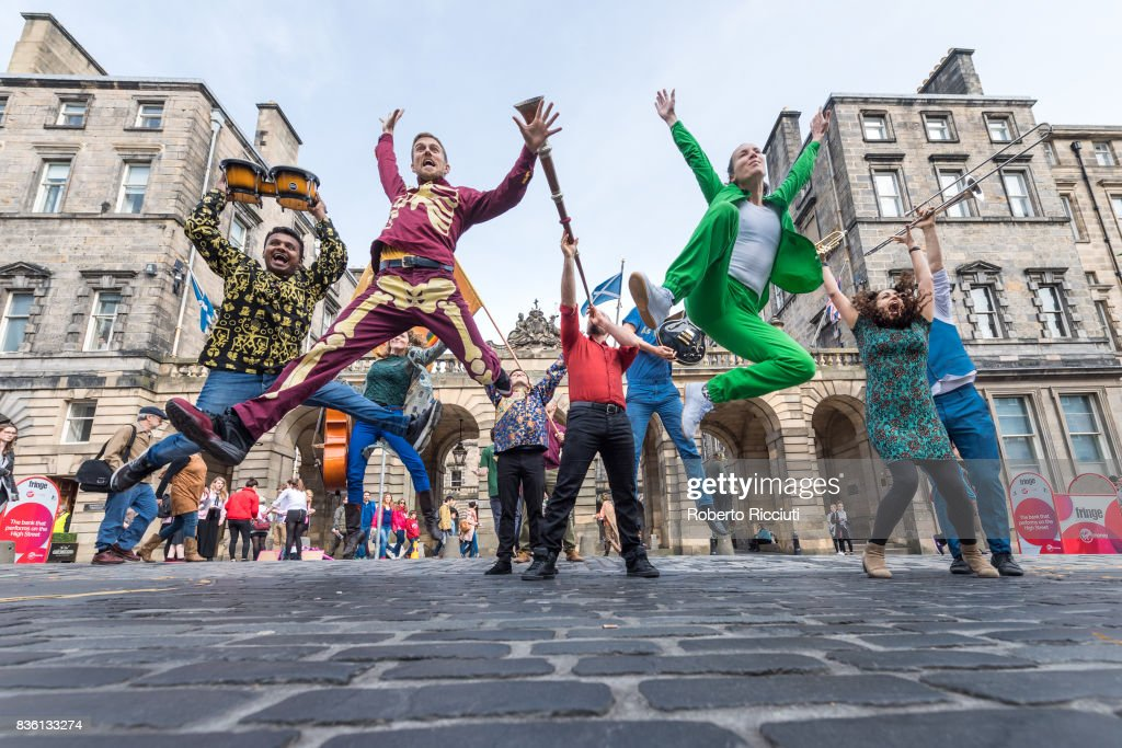 Entertainers from company Massive Vibe Live! jump in front of City Chambers to promote their show 'Perfect as you are' on the Royal Mile during the 70th Edinburgh Fringe Festival on August 21, 2017 in Edinburgh, Scotland.