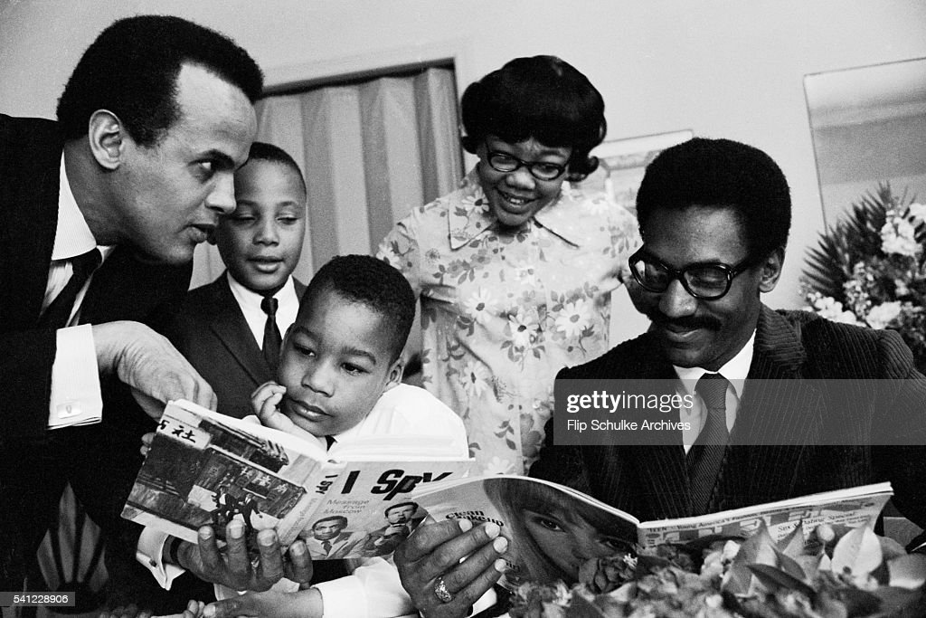 Entertainers Harry Belafonte (left) and Bill Cosby read books and magazines with Martin Luther King, Jr.'s children after their father's assassination.