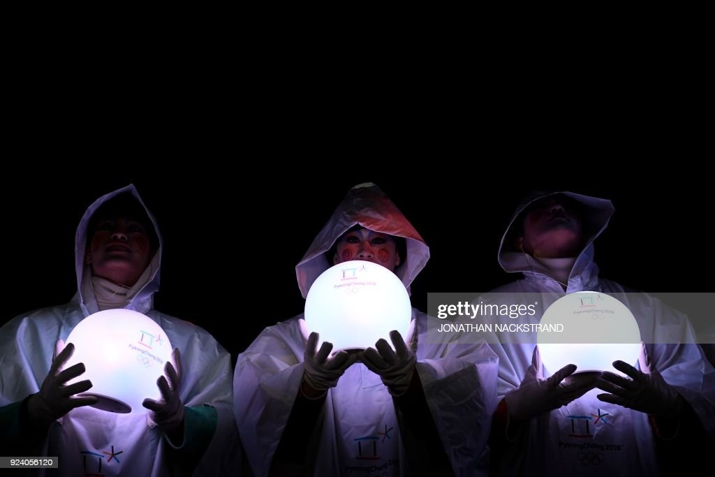 Entertainers hold lit globes during the closing ceremony of the Pyeongchang 2018 Winter Olympic Games at the Pyeongchang Stadium on February 25, 2018. / AFP PHOTO / Jonathan NACKSTRAND