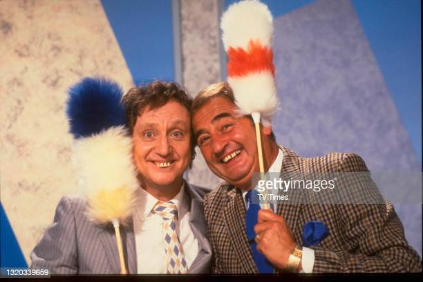 Entertainers Ken Dodd and Bernie Winters posed with 'tickle stick' props during an appearance on game show 3-2-1, circa 1986.