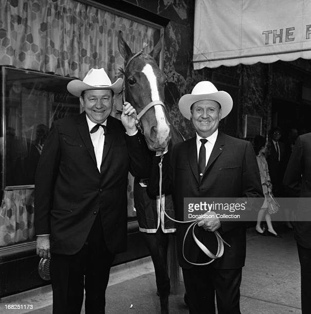 Entertainers Tex Ritter and Gene Autry pose for a portrait with the horse named Country Music which was the door prize of the day for the Country...