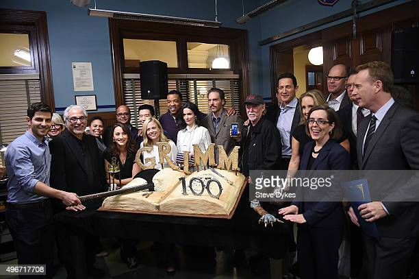 NBC Entertainment chairman Robert Greenblatt and Oregon governor Kate Brown pose with the cast of the TV series Grimm next to the cake celebrating...