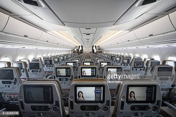 Entertainment monitors sit on the back of passenger seats in the economy class cabin of an Airbus SE A350 aircraft operated by Singapore Airlines Ltd...