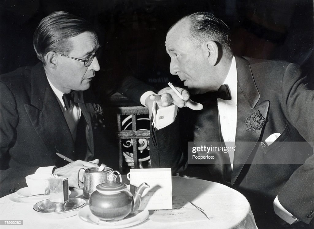 circa 1950's, English actor, producer and director Sir Noel Coward, right, talking to reporter MacDonald Hastings at the Cafe de Paris, London