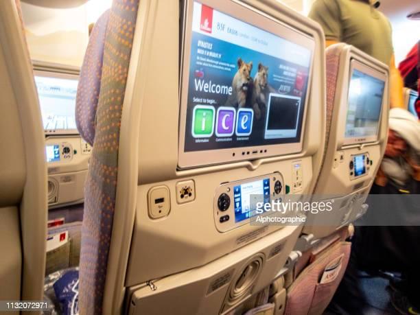 underhållnings system på bak sidan av sätet på en kommersiell lång distans flygning - film and television screening bildbanksfoton och bilder