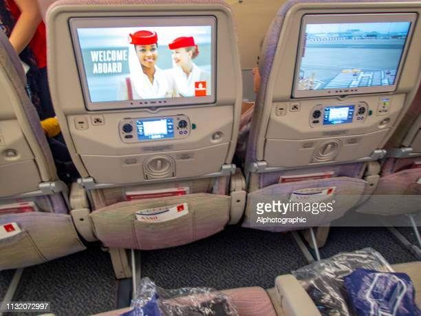 entertainment system in the back of the seat on a commercial long haul flight - film screening stock pictures, royalty-free photos & images