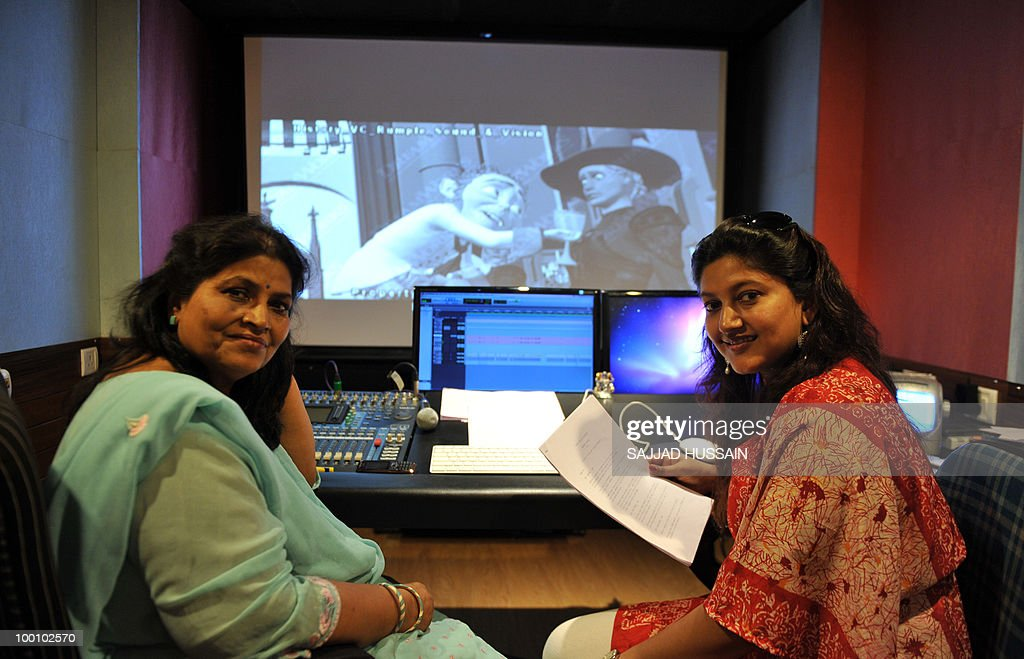 Entertainment-India-film-industry-US-Hollywood,FEATURE by Phil Hazlewood Indian voice artiste Mona Shetty (R) poses with her mother Leela Ghosh at their dubbing studio in Mumbai on May 12, 2010. The dubbing business is taking off in India with the increasing popularity of Hollywood films among domestic audiences, with analysts seeing it as a key emerging market for US films. Shetty, who runs a dubbing studio with her mother in the north of India's entertainment capital, has given her voice to some of Hollywood's most bankable female stars, like Angelina Jolie, Drew Barrymore, Cameron Diaz and Catherine Zeta-Jones. AFP PHOTO/Sajjad HUSSAIN